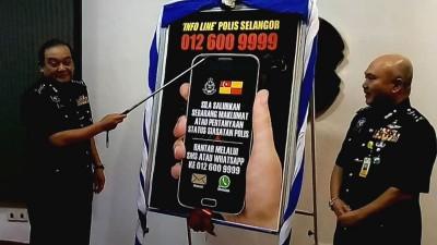 马兹南(左)周四推介警方新的的智能手机热线号码,右是雪州副总警长拿都阿都拉昔。