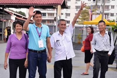 陈志忠(中)与妈妈李素满(左起)及爸爸陈金发一同履行公民责任。