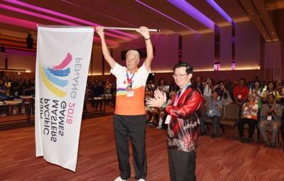 曹观友把APMG旗帜移交给亚太区运动会协会主席凯赫。