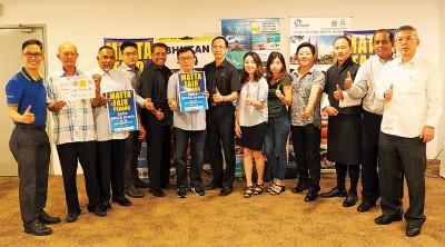 马来西亚游览总会首席执行官潘在会(左6)、望秘书长王振添(着)同参展商们欢迎大家踊跃出席马来西亚国际旅游展。