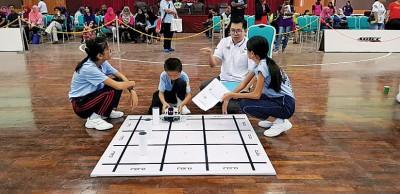 学生互相配合将机械人赛题完成。
