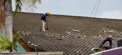 工友在有些礼堂屋顶上清理碎瓦片。
