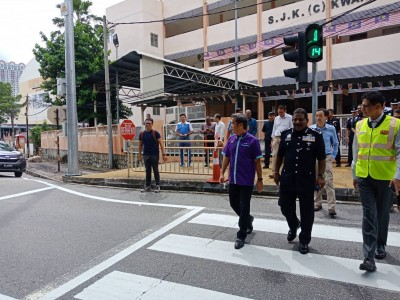 尤端祥(左起)、达威甘及沙哈布丁也亲自试用行人交通灯。\