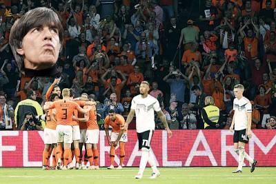 (小图)勒夫。德国吞下了今年的第5场败仗后落寞离场与相拥庆祝的荷兰队形成对比。