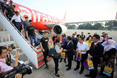 乘亚航飞机从柔佛士乃到怡保的搭客下机时中陈家兴(前排右起)、拉惹阿兹米、阿末法依沙之迎。