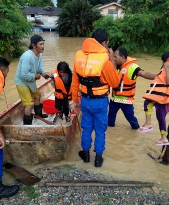 民防局人员利用小船疏散受困的甘榜居民。