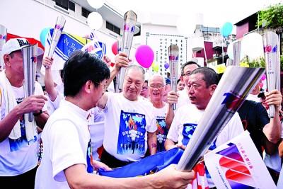 郑奕南(中)接领其中一支火炬,右起是王孙文、杨旺成。