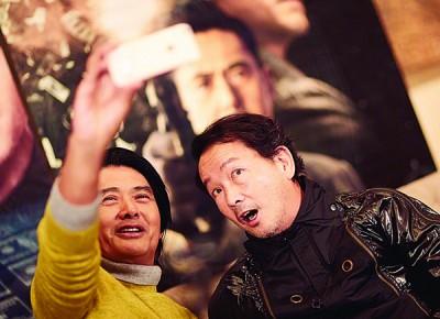 周润发(左)携廖启智在北京玩自拍。