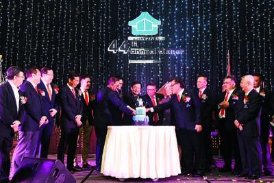 曹观友(中)与马来西亚房地产发展商槟州分会理事共切喜糕。