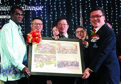 筹委会主席方振忠(右)赠送画册给救世军孤儿院的代表法兰西斯。