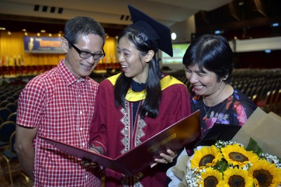 蔡玉恬(中)开心的与双亲分享自己获得的大学毕业证书。