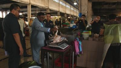 苏姆甘在双溪大年国内贸消执法局员陪同下,逐一检查老街场大巴刹佳节物品价格,右为马兹兰。
