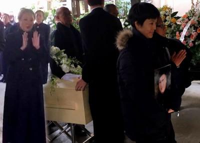 岳华告别仪式,女捧着父亲遗照护送棺木前往火化。