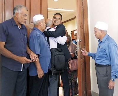 莫哈末阿南获无罪释放后,步出法庭时开心拥抱亲友。