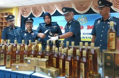 朱基菲(右2)展示起获的走私烈酒。