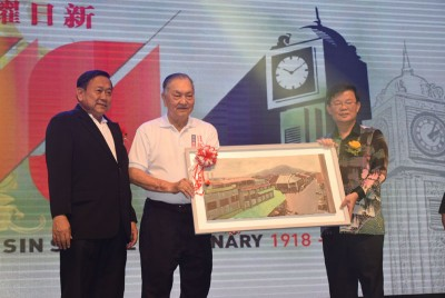 郑奕南(中)在庄佛和(左)陪同下,赠送校友陈毓康画家的大山脚市区街景画作给曹观友。