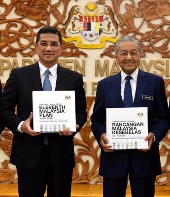 马哈迪周四亲自向国会下议院提呈备受瞩目的第11大马计划中期检讨报告。旁为经济事务部长阿兹敏阿里。