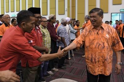 末沙在为联邦直辖区和敦拉萨镇诚信党党部主持开幕时,与党员握手慰问。