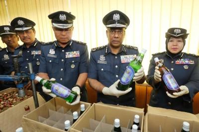 苏博马廉(右2)与关税局官员向媒体展示所起获的私酒。