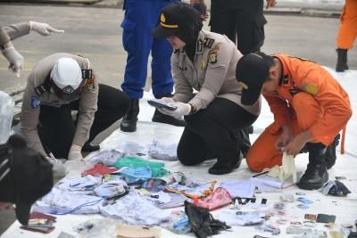 警方及搜救人员忙着鉴定打捞起的遇难者随身物品。(法新社照片)