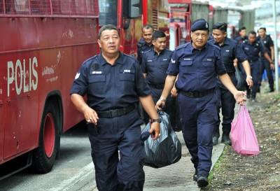两名警员从斯里马哈马里安曼兴都庙带走垃圾。