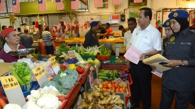 阿都哈林在贸消局官员的陪同下巡视敦沙顿巴刹,以了解当地贩商们是否有根据政府所设的统制品价格行商。