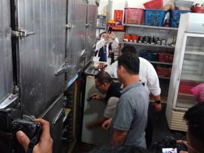 执法人员正在检查该点心楼内的冰箱。