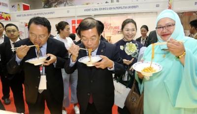"""陈国伟(中)为""""一带一路""""陕西特色商品展览会开幕后,品尝参展的美食。"""