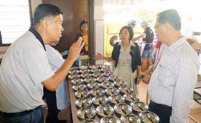 唐进顺(左)向周成祝讲解营养餐计划,右2是黄基金校长。