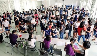 槟华小学礼堂内可见大批学生在成就放榜之际,陆续排队领取成绩单。