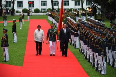 菲律宾总统迪泰特(眼前左)陪伴中国国家主席习近平(眼前右)检阅仪仗队。(法新社照片)