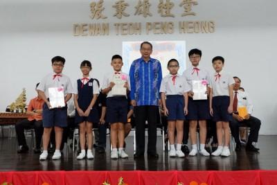 林祥泰(中)在上周出席三山小学毕业典礼,颁发毕业证书予各班毕业生代表。