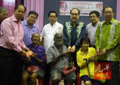 林祥泰(后排右1)与槟华堂福利组员在新春期间,分派红包给乐龄人士。
