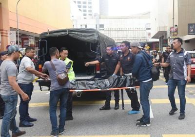 警员准备将死者遗体送往太平间停放。