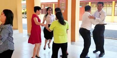 公华老师在视频中手握手跳起圈圈舞欢庆,以迎接学校假期。