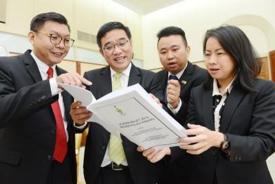 特别前来州议会探班的升旗山区国会议员黄汉伟(左2)与州议员郑来兴(左起)、黄顺祥及王丽丽一同翻阅《2019年槟州财政预算案》。