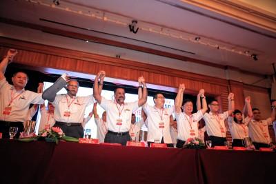 罗兴强(左起)、拉玛沙米、佳日星、林冠英、曹观友、再里尔、林慧英和黄汉伟高举双手,呼吁党员力保槟城江山。