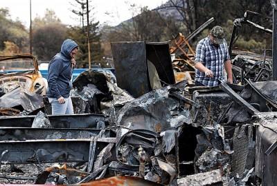 灾民在已经被烧毁的住家废墟中,寻找可用的东西。(法新社照片)