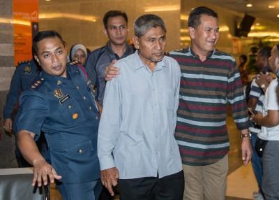 死者父亲莫哈末卡欣(中)周二(18日)凌晨在旁人的陪同下,神情哀伤地离开国家心脏中心。