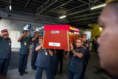 死者同僚将死者灵柩抬入直升机。