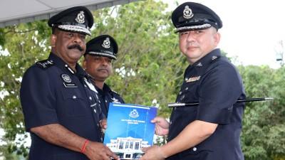 达威甘(左起)颁发褒奖状予西南县行政部主任陈锭钏警监,由安峇拉甘(中)陪同见证。