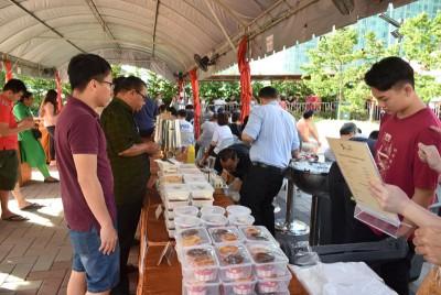工作人员售卖餐饮,让民众充饥。