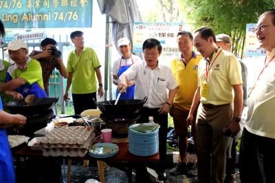 首长拿起锅铲,手势俐落地在义卖会现场炒粿条。