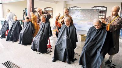 法师们为参与者剃度。