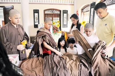 何君舰夫妇为儿子挑选合适的僧服。