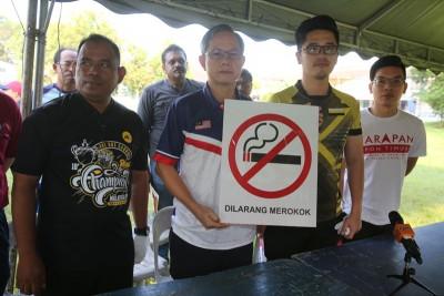 李文材(左2)展示标准的香烟告示牌,左起札冠、李存孝,怡保市议员吴耀君。