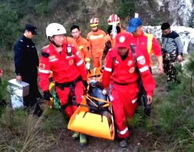 救援人员用担架将两人运送下山。