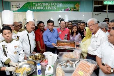 众多嘉宾巡视珍珠食物银行的中央厨房。