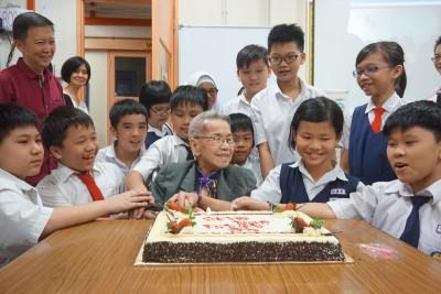 小学生在朱校长回校日当天,与她一起欢庆生日。(档案照)