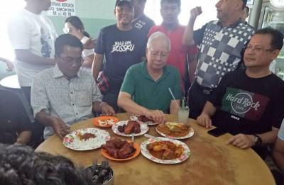 前首相纳吉周六在怡保著名的扁担饭档品尝美食。